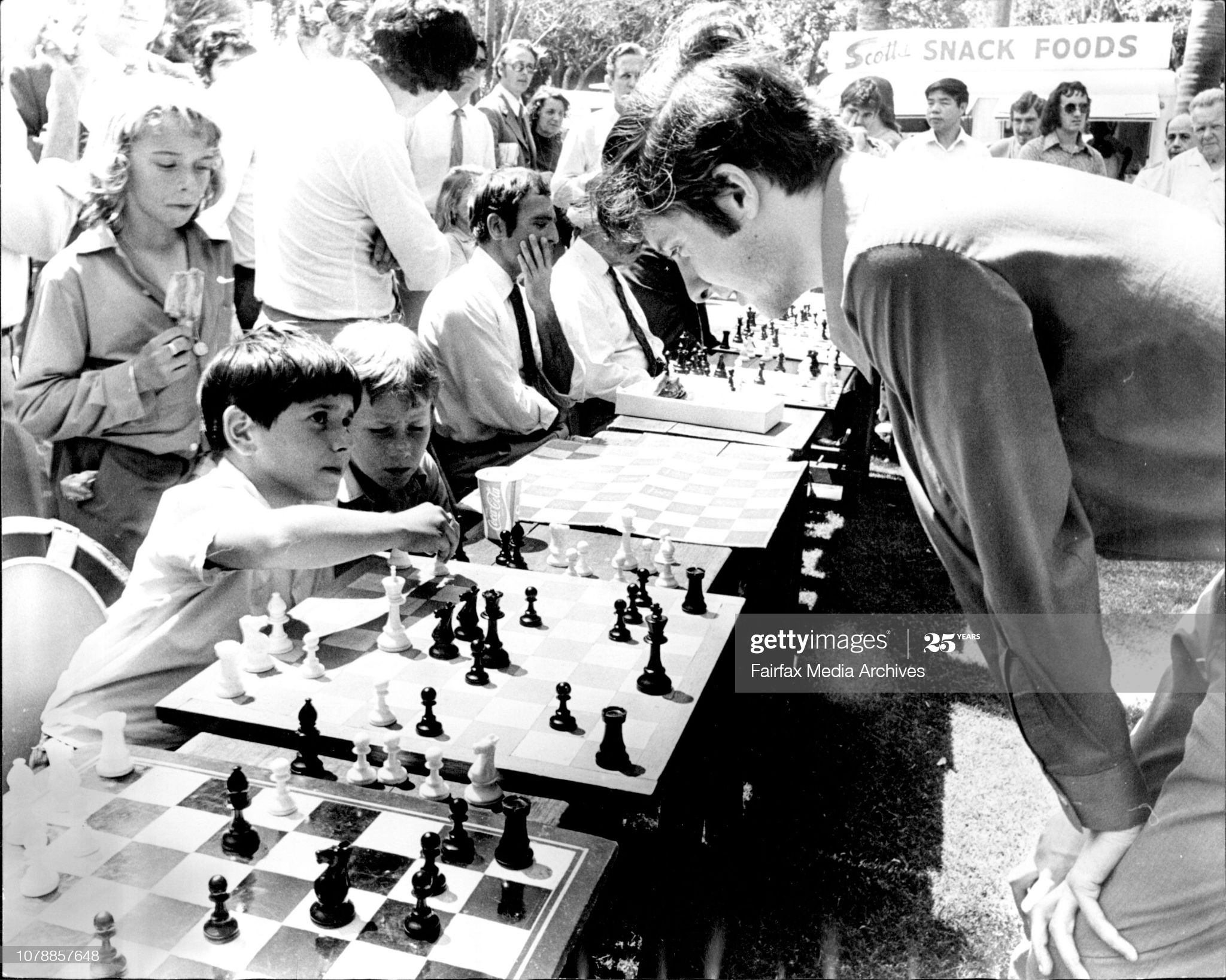 Aleandro Trimboli (10) of Leichhardt plays Mr Max Fuller of Newtown, Australian Open Chess Champion. As part of the Waratah Festival Celebrations the NSW Chess Association is conducting chess games with chess champions playing up to 30 players at once, in Hyde Park. October 17, 1973. (Photo by Golding/Fairfax Media via Getty Images).