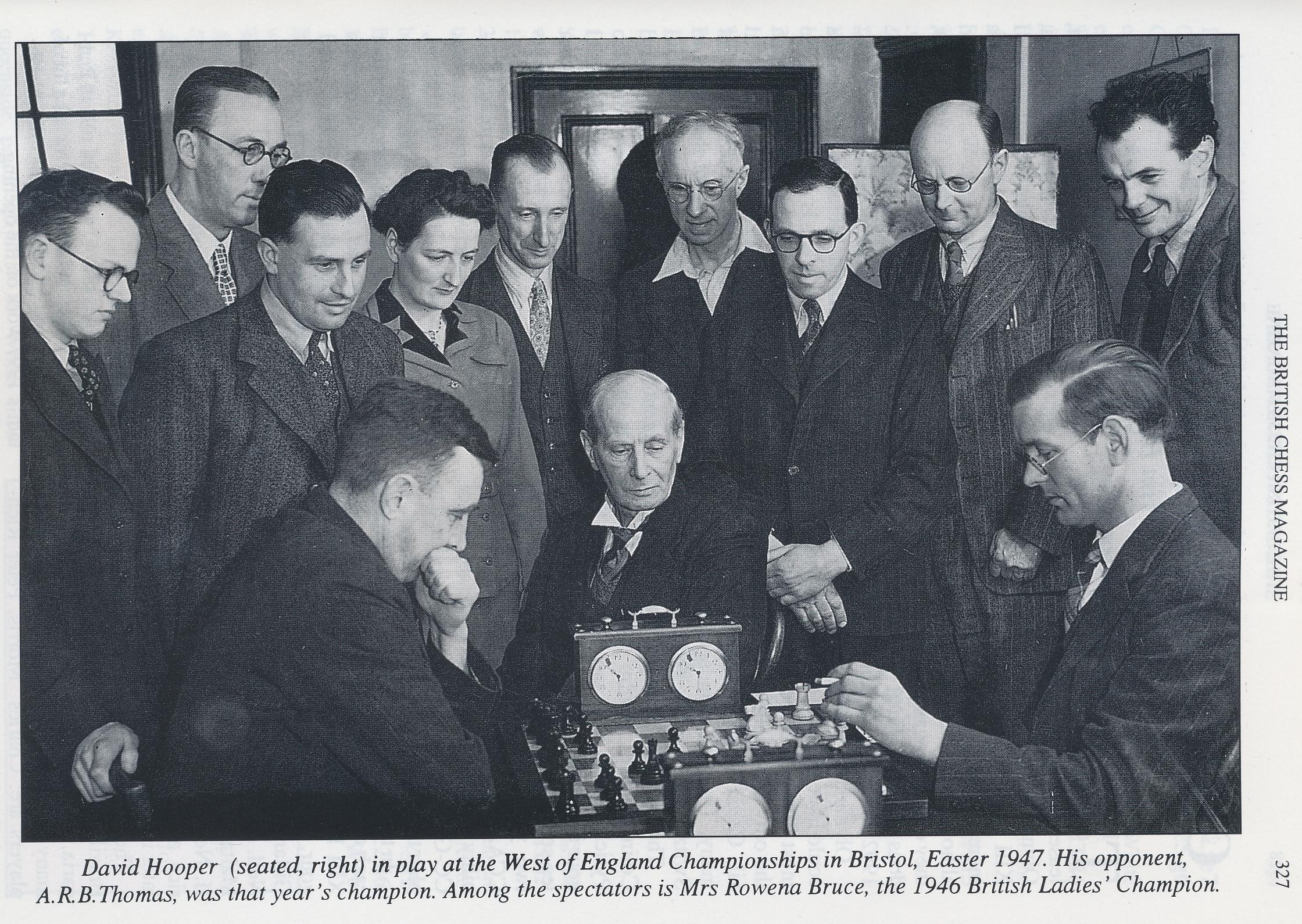 David Hooper (seated right) in play at the West of England Championships in Bristol, Easter, 1947. His opponent , ARB Thomas , was that year's champion. Among the spectators is Mrs. Rowena Bruce, the 1946 British Ladies' Champion. BCM, Volume 118, #6, p.327. The others in the photo are L - R: H. V. Trevenen; H. Wilson-Osborne (WECU President); R. A. (Ron) Slade; Rowena Bruce; Ron Bruce; H. V. (Harry) Mallison; Chris Sullivan; C. Welch (Controller); F. E. A. (Frank) Kitto.