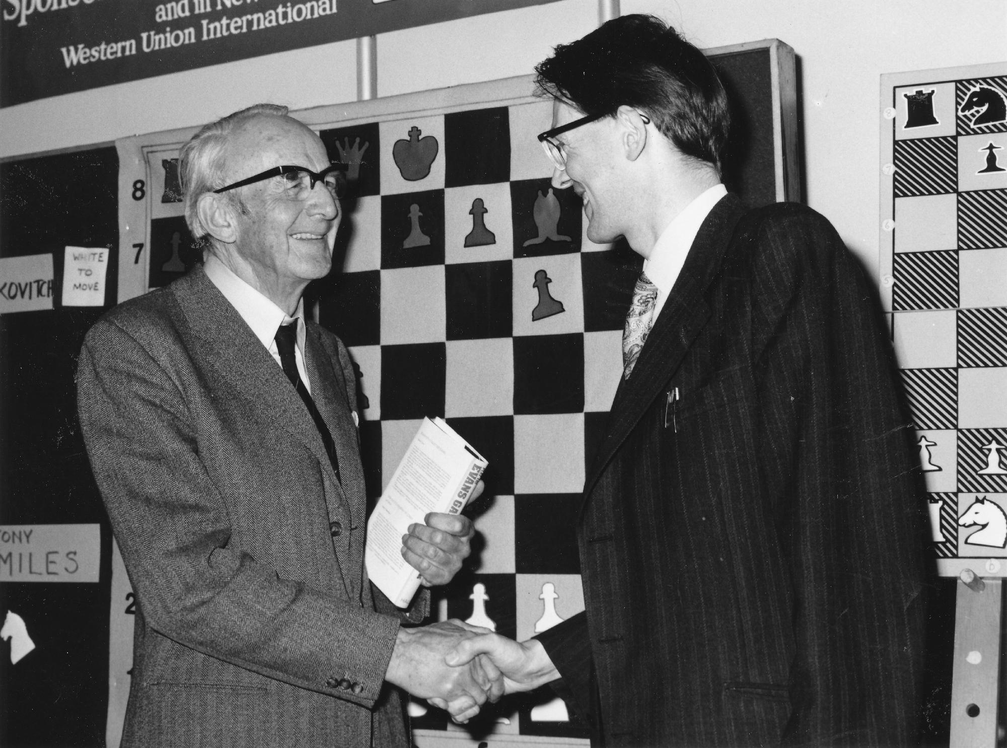 "David Anderton (rhs) congratulates Sir Philip Stuart Milner-Barry for winning the ""Board of Honour "" game versus Edward Lasker at the 1976 Lloyds Bank Match by Telex, London - New York. From BCM, volume XCVI (96) Number 11 (August), Page 494. The venue was the Bloomsbury Hotel, London. Photo courtesy of Lloyds Bank"