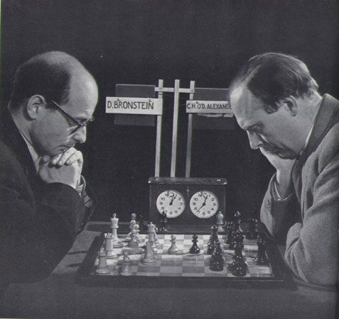 Staged publicity picture of David Bronstein vs Hugh Alexander at Hastings 1953