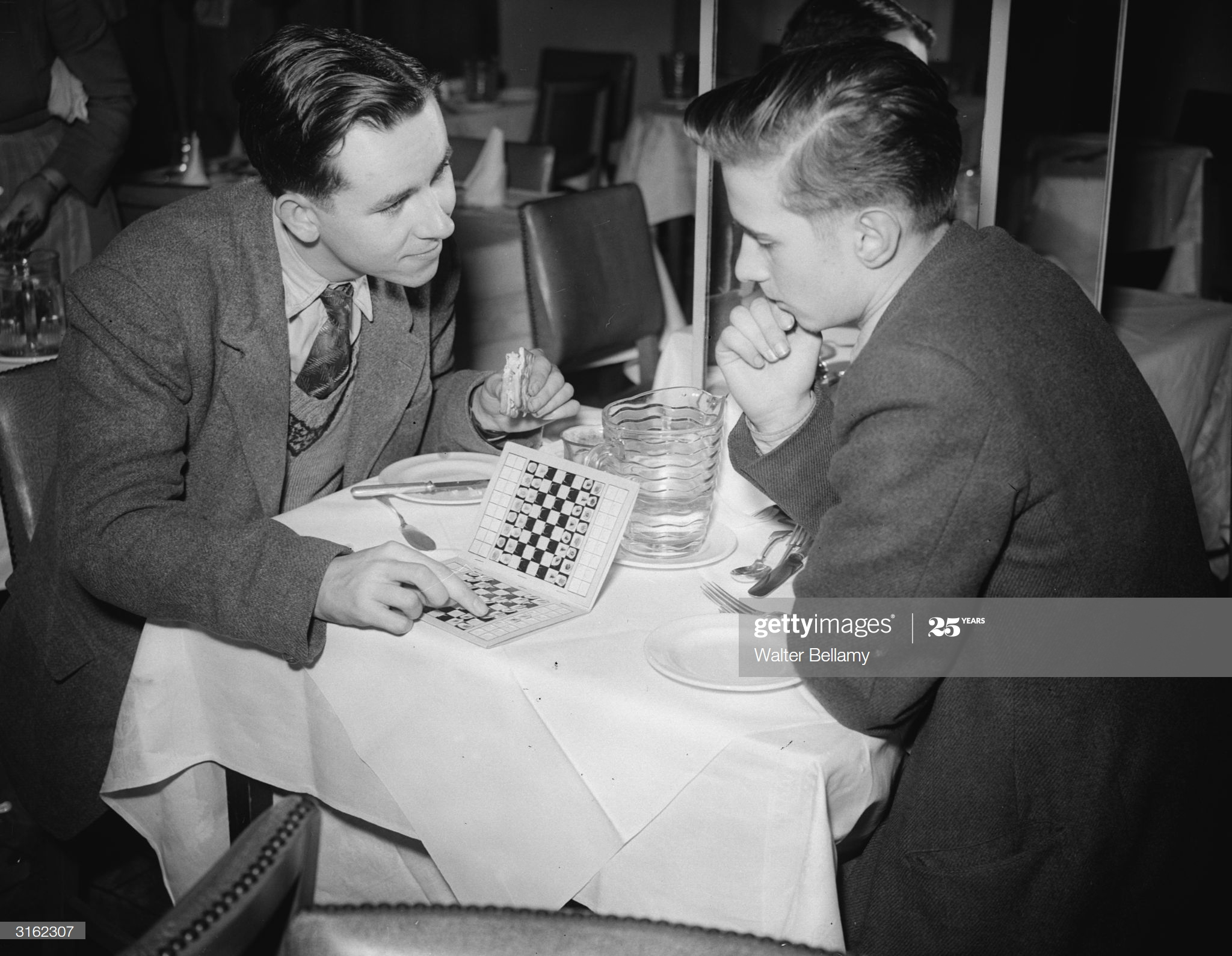 Travel Chess 2nd January 1951: British chess champions Jonathan Penrose and Leonard Barden ponder over a portable travel game in a restaurant. (Photo by Walter Bellamy/Express/Getty Images)