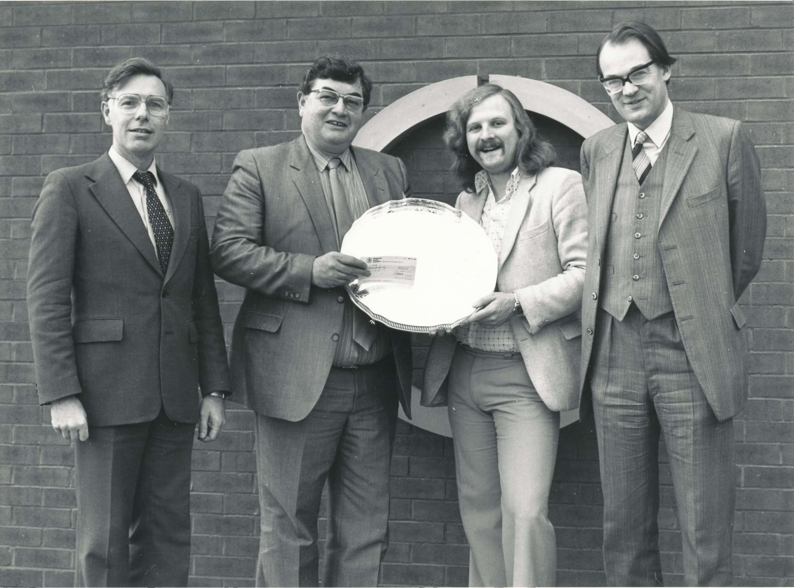 Tony receives the 1984 Leigh Grand Prix award from Dr. A Kent, Malcolm Wood (Chief Executive) and David Anderton OBE