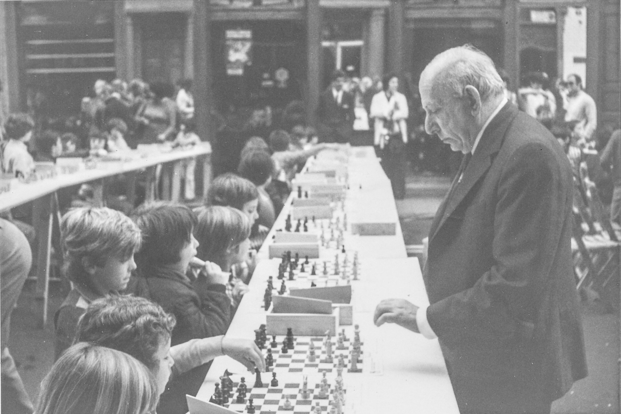 "Harry was invited because it was the 50th anniversary of his victory in the London Boys 1929 a success which he often referred to in his <em>Times</em> column. There were seven 30-board simuls that day, the top three being England Juniors v USSR (Spassky, Vasyukov, Kochiev) where Spassky had the worst simultaneous result of his career. No 4 was by <a href=""http://britishchessnews.com/2020/04/04/happy-birthday-gm-murray-graham-chandler-mnzm-04-iv-1960/"">Murray Chandler</a>, Harry was No5 and the others by <a href=""http://britishchessnews.com/2020/07/07/bcn-remembers-im-andrew-whiteley-09-vi-1947-07-vii-2014/"">Whiteley</a> and <a href=""http://britishchessnews.com/2020/07/08/remembering-fm-david-edward-rumens-23-ix-1939-08-vii-2017/"">Rumens</a>. The juniors who played the Russians were personally invited."