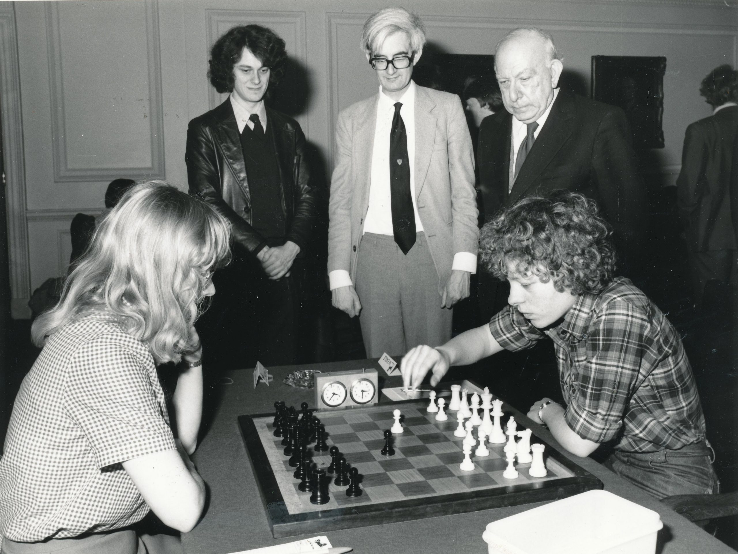 "Linda Brownson (Newnham & Basildon), left, playing Maria Eagle (Pembroke & Formby) being observed by John Nunn, Adrian Hollis and Harry Golombek posing for the obligatory ""staring at the board"" picture for the 1981 Varsity Match sponsored by Lloyds Bank."