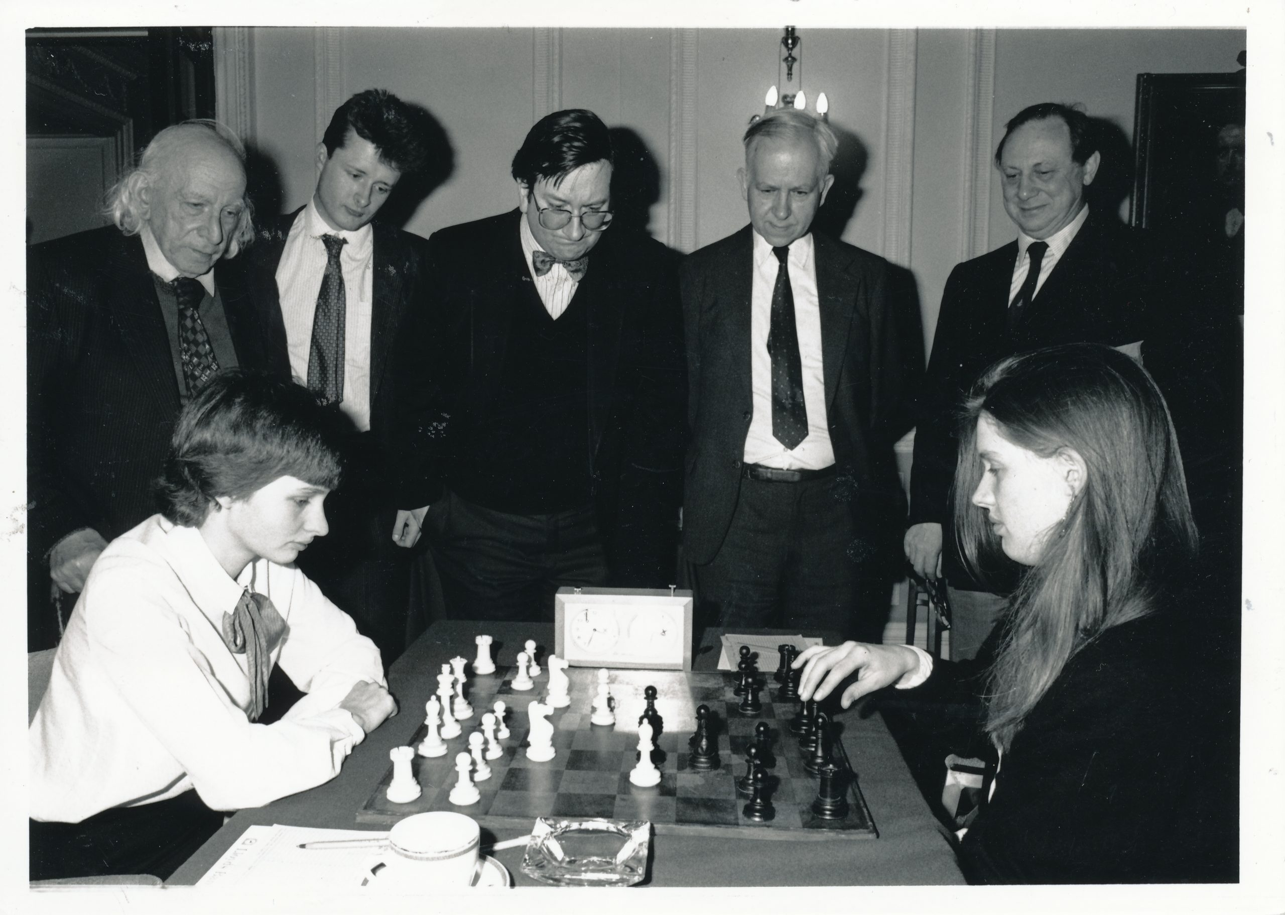 "Harry Golombek, Peter Wells, Ray Keene, Leonard Barden and henry Mutkin take part in the obligatory ""Staring at the board"" posed picture during the 1985 Varsity Match"
