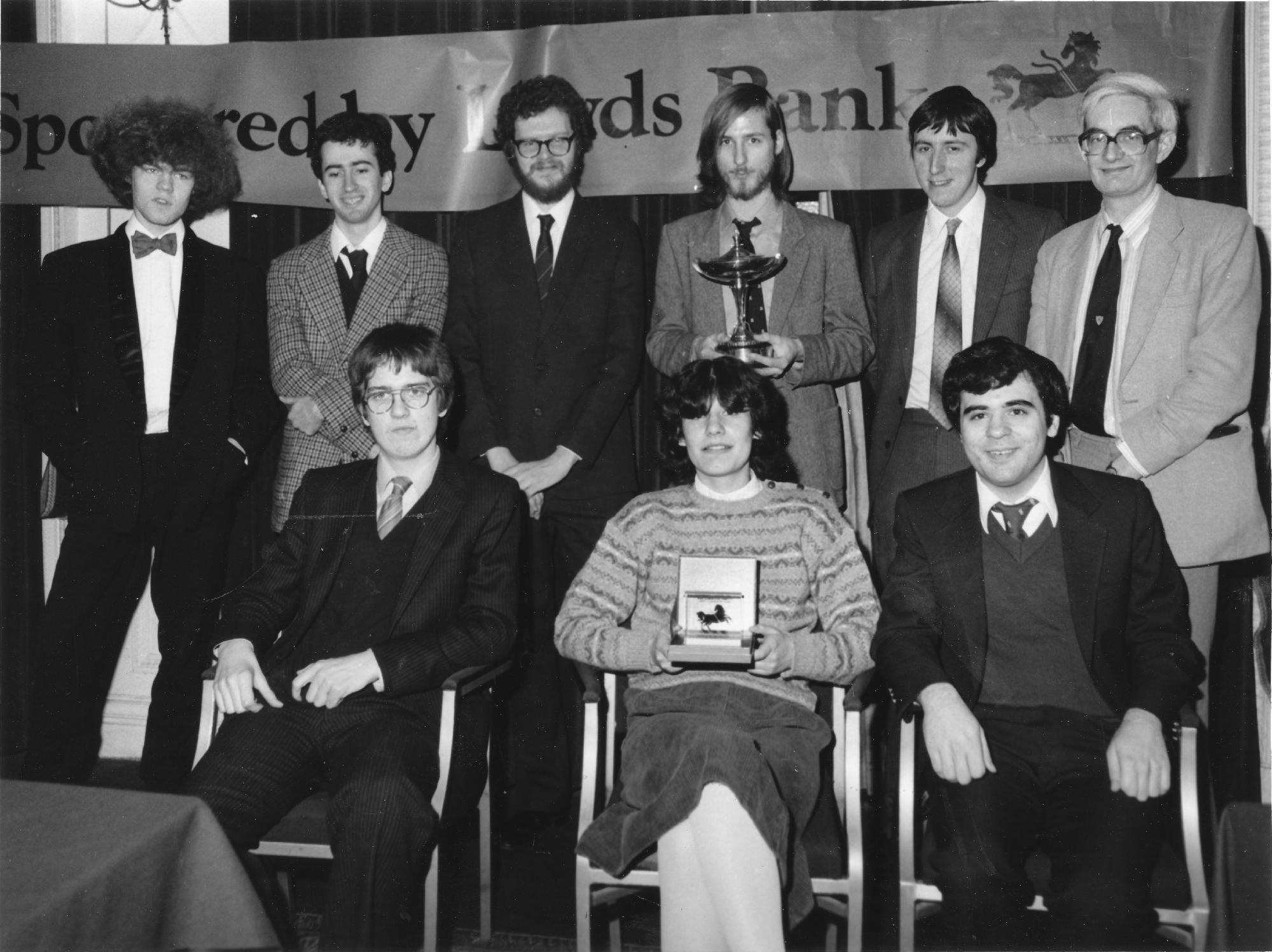 Erik Teichmann standing, holding trophy)
