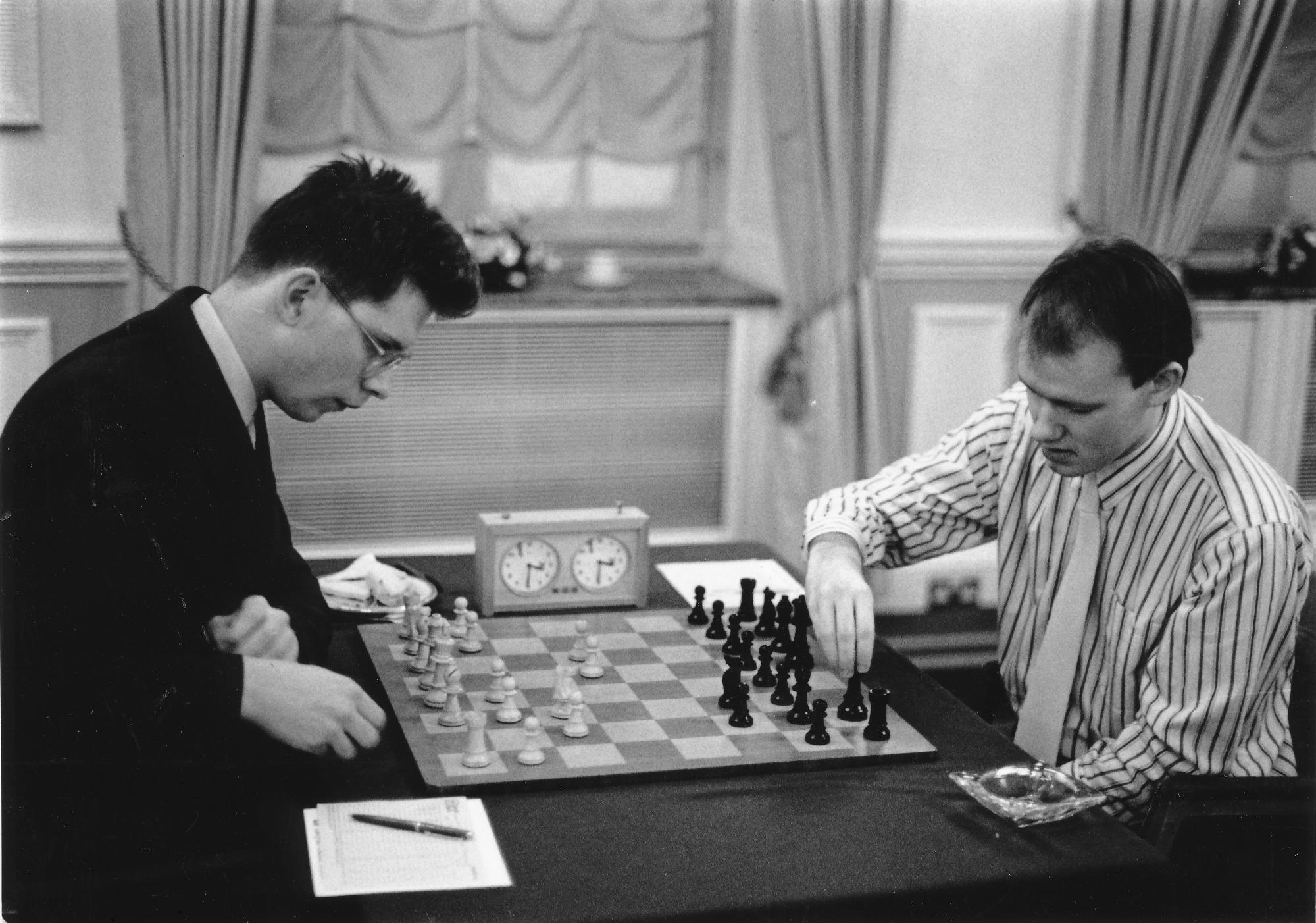 Oxford's IM James Howell (l) shapes up against Cambridge's FM Graham Burgess on top board in the Lloyds Bank Varsity match which Cambridge won 5.5 - 2.5. The players reeled off 19 moves of Yugoslav King's Indian theory before Howell established a dominant B vs N which won the Lloyds Bank trophy for the best Oxford game. Photograph by Lloyds Bank.