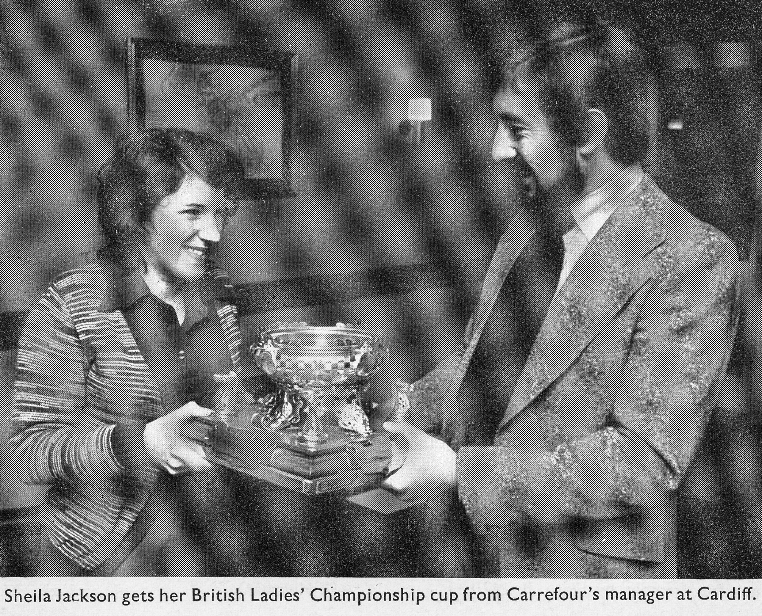 Sheila Jackson gets her British Ladies' Championship cup from Carrefour's Manager at Cardiff. Source : CHESS, Volume 41, Numbers 739-4, page 137.