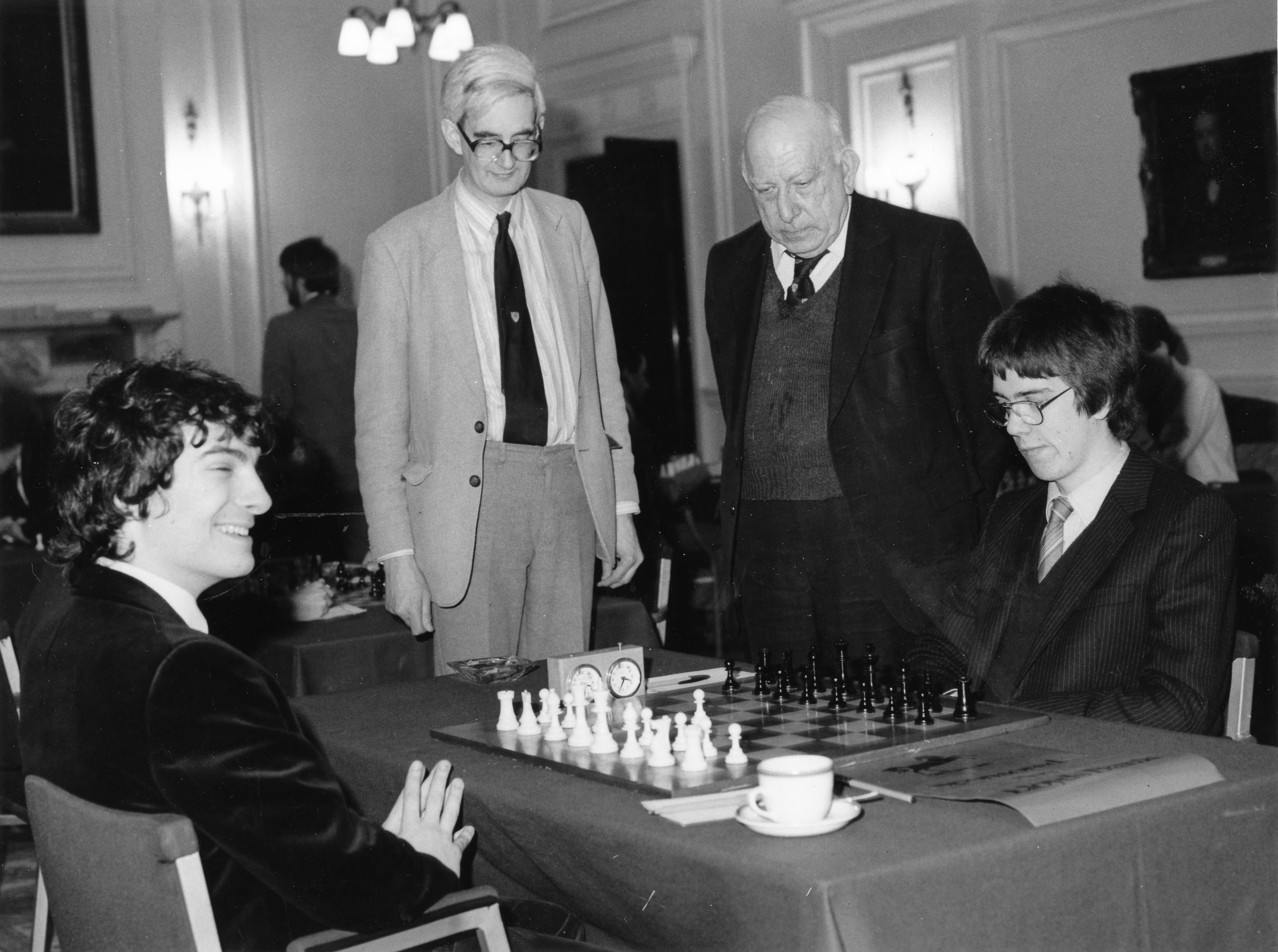 Adrian Hollis and Harry Golombek observer Andrew Dyson (Trinity) having played 1.d4 versus IM William Watson (Merton) during the 1984 Varsity match sponsored by Lloyds Bank