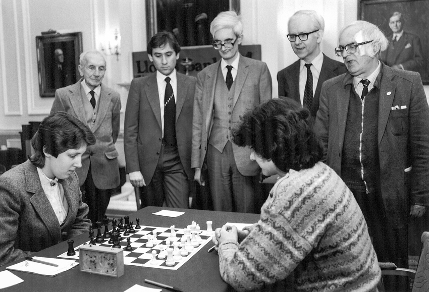 From the 1985 Varsity Match : Laura Cohen (Newnham), Brian Reilly (BCM), Bill Hartston (Cambridge), Adrian Hollis (Oxford), Anita Rakshit (St. Hilda's), Leonard Barden (The Guardian etc) and Bob Wade (BCF)