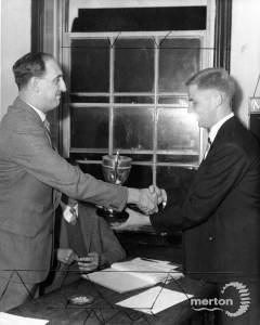Mr A Corish (right), receives the Chess Champion cup from Mr J Adams. 18th September 1958 from the Merton Advertiser, Photographer unknown.