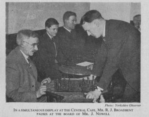 In simultaneous play at the central cafe, Mr. RJ Broadbent pauses at the board of Mr. J. Nowell, original source : The Yorkshire Observer
